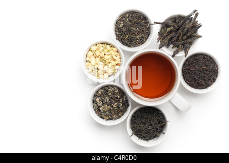 Black Tea in White Cup with tea leaves and flowers. - Stock Photo