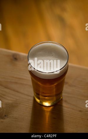 pint of british beer on pub table - Stock Photo