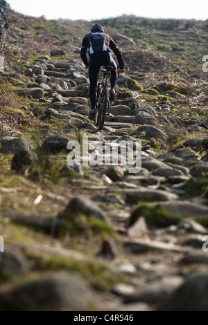 Irish mountain biking champion Robin Seymour rides up a rocky trail, County Wicklow, Republic of Ireland - Stock Photo