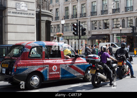 London taxi cab and motorcycles on Great Marlborough Street, London, England - Stock Photo
