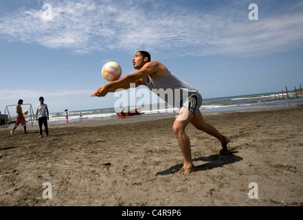 Group of friends playing volleyball on a beach on the Caspian Sea at Bandar-e Anzali, Iran - Stock Photo