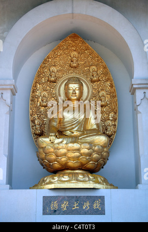 Golden Buddha statue (Enlightenment) in the north niche of the Japanese Buddhist Peace Pagoda, Battersea Park, London, - Stock Photo