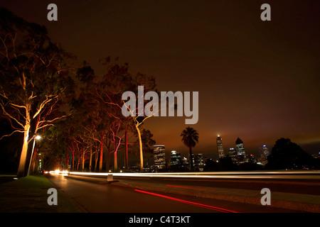 Illuminated Lemon-scented eucalyptus gum trees in Kings Park at night with Perth skyline, Western Australia, Australia - Stock Photo