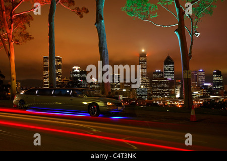 Stretch Limousine Under Light Painted Lemon Scented Eucalyptus Gum Trees in Kings Park at Night and the Perth City - Stock Photo