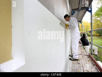 Heat insulation of a building. For saving energy, Styrofoam panels are sticked to the outside wall, to keep the - Stock Photo