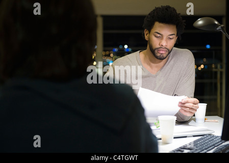 Colleagues working on project together in office at night - Stock Photo