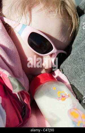 Baby girl lying down, drinking milk from bottle - Stock Photo