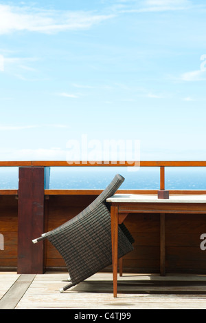 Wicker chair leaning against table on deck - Stock Photo