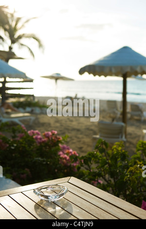 Ashtray on table at beach, beach umbrellas and deckchairs in background - Stock Photo