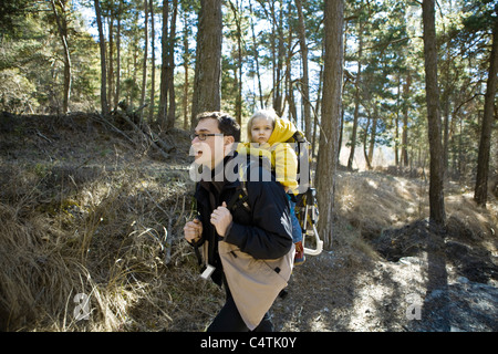Father hiking in woods with baby daughter in backpack carrier - Stock Photo