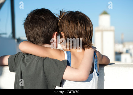 Young siblings with arms around each other's shoulders, rear view - Stock Photo
