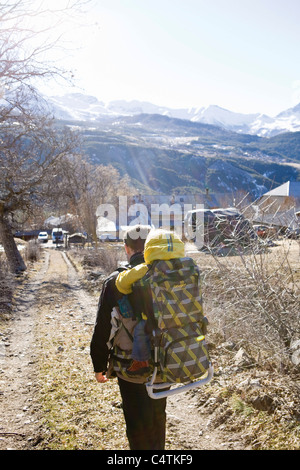 Father hiking on trail, carrying baby in backpack - Stock Photo