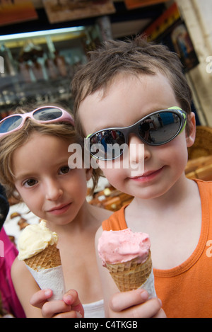 Young siblings eating ice cream cones - Stock Photo