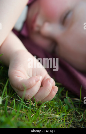 Baby girl napping on grass - Stock Photo