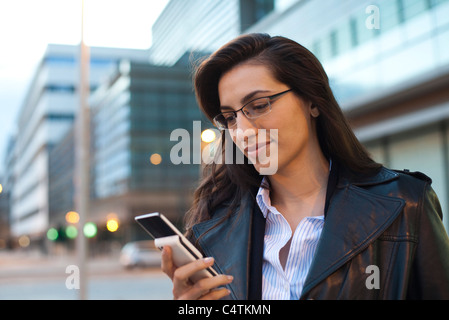 Businesswoman using cell phone, portrait - Stock Photo