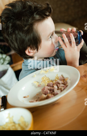 Little boy at table, drinking glass of water - Stock Photo