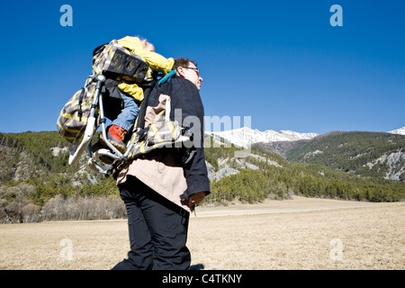 Father hiking with baby in backpack carrier - Stock Photo