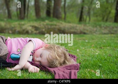 Toddler girl taking a nap outdoors - Stock Photo