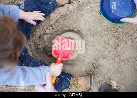Toddler boy playing in sand - Stock Photo