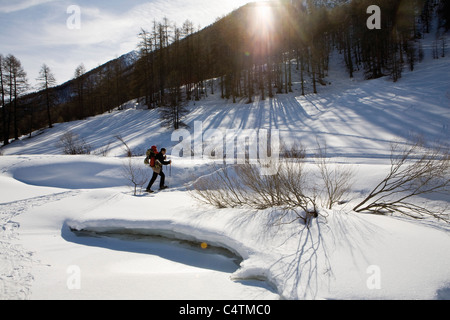 Man snowshoeing, carrying child in baby carrier - Stock Photo