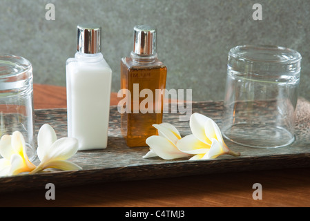 Perfume bottle and glasses on tray with frangipani flowers - Stock Photo