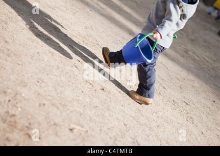 Little boy walking with sand bucket - Stock Photo