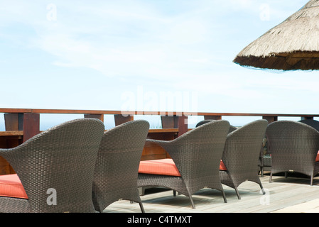 Wicker chairs lined up along deck - Stock Photo