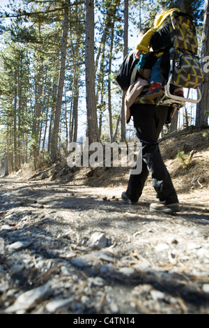 Hiker walking in woods with baby in backpack carrier, low angle view - Stock Photo