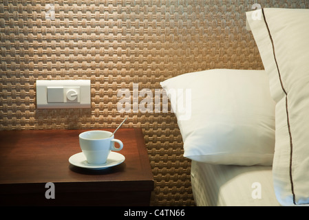 Coffee cup on bedside table - Stock Photo