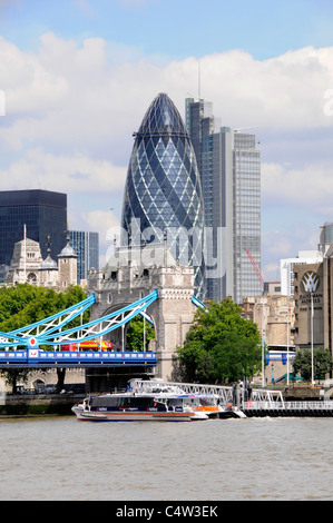 Thames clipper boat public transport service River Thames with City of London skyline Gherkin & Heron Tower skyscraper - Stock Photo