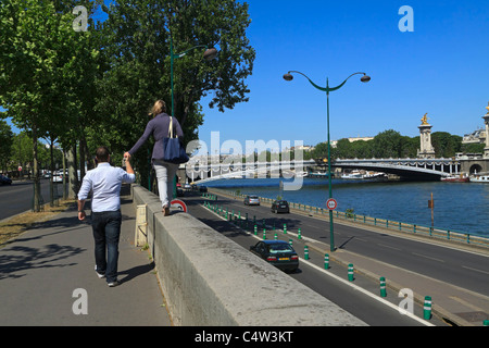 Sightseeing in Paris. A couple walk along the Quay D'Orsay beside the Seine River towards Pont Alexandre III. - Stock Photo