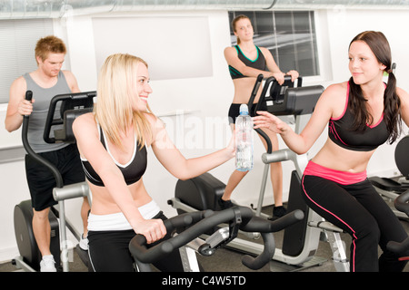 Fitness young girl on gym bike - crosstrainer in background - Stock Photo