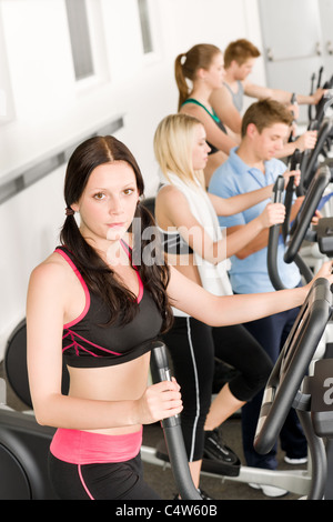 Fitness young group on elliptical cross trainer at health gym - Stock Photo