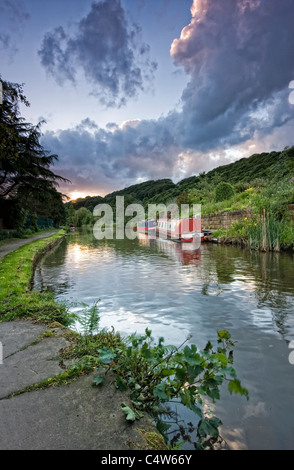 canal narrowboat on the rochdale canal sidelit by the warm glow of sunset - Stock Photo