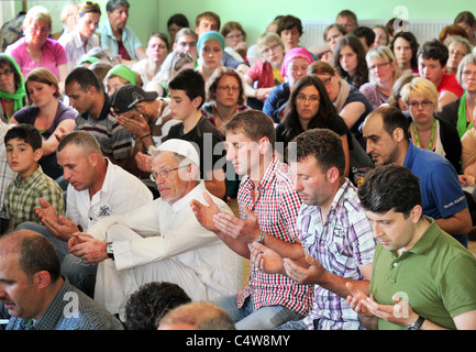 turkish muslims (front) watched by german christians (back) during a friday prayer in a mosque in Dresden, Germany. - Stock Photo