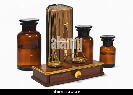 Detail photo of a old druggist balance alongside are three pharmacists bottles and a old book - Stock Photo