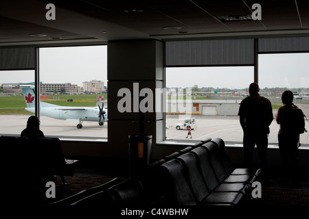 Passengers watch airport crew operation on an Air Canada DHC-8-402 aircraft at Montreal Pierre Elliott Trudeau airport - Stock Photo