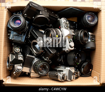 a cardboard box of assorted used old second hand 35mm old film SLR camera bodies and lenses, UK - Stock Photo