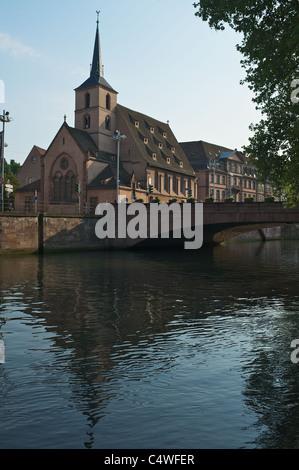 Strasbourg : Quai Saint-Nicolas, Protestant Church of Saint-Nicolas reflected in channel with bridge - Stock Photo