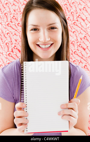 USA, New Jersey, Jersey City, Portrait of smiling young woman holding blank notebook - Stock Photo