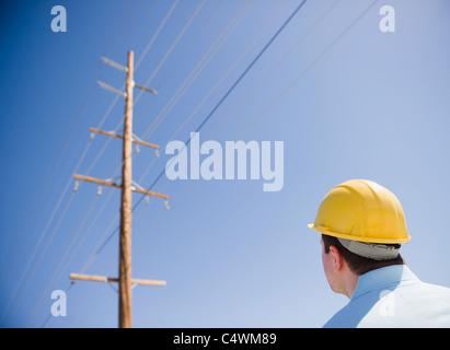 USA, California, Palm Springs, Coachella Valley, San Gorgonio Pass, Man in hard hat looking at telephone pole - Stock Photo