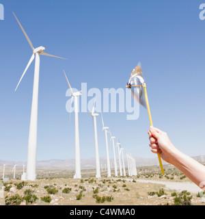 USA,California,Palm Springs,Coachella Valley,San Gorgonio Pass,Woman's hand holding pinwheel against blue sky and - Stock Photo