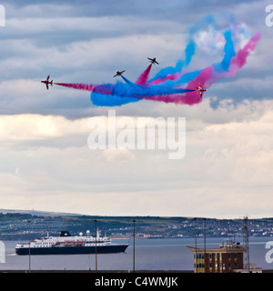 Red Arrows in formation over Leith Harbour and visiting cruise ship Minerva, Armed Forces Day, June 24 2011, Edinburgh, - Stock Photo