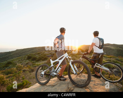 USA,California,Laguna Beach,Two bikers on hill looking at view - Stock Photo