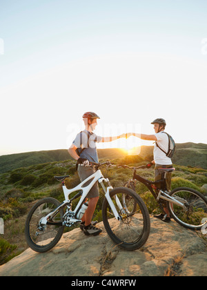 USA, California, Laguna Beach, Two bikers on hill doing fist bump - Stock Photo