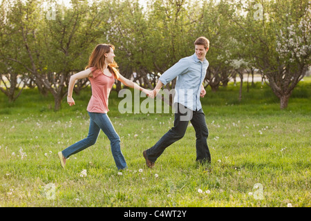 USA,Utah,Provo,Young couple running through orchard - Stock Photo