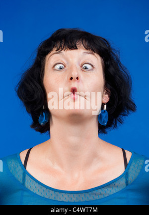 middle-aged woman making funny faces - isolated on blue - Stock Photo