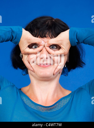 middle-aged woman making funny gesture - isolated on blue - Stock Photo