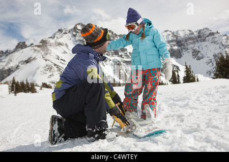 USA,Colorado,Telluride,Father helping daughter (10-11) with snowboard binding - Stock Photo