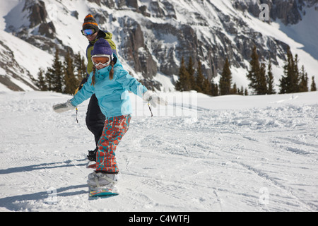 USA,Colorado,Telluride,Father and daughter (10-11) snowboarding - Stock Photo